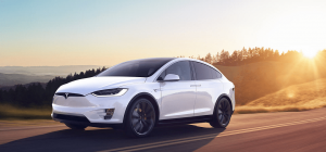Tesla Model X white highway sun