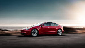 tesla model 3 red road sun